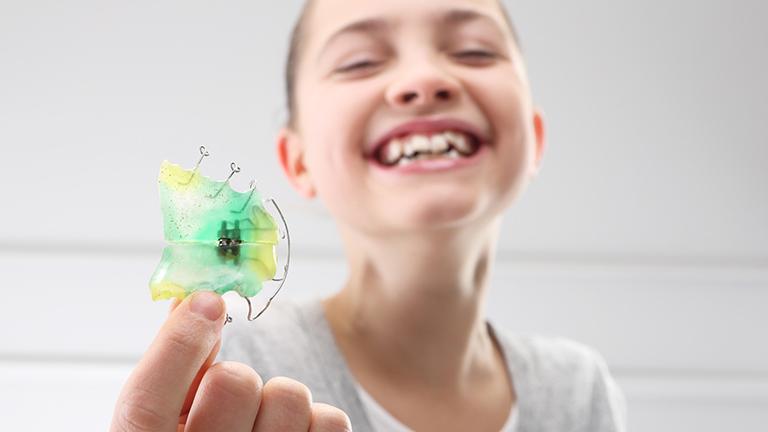 adolescente con ortodoncia removible en manos